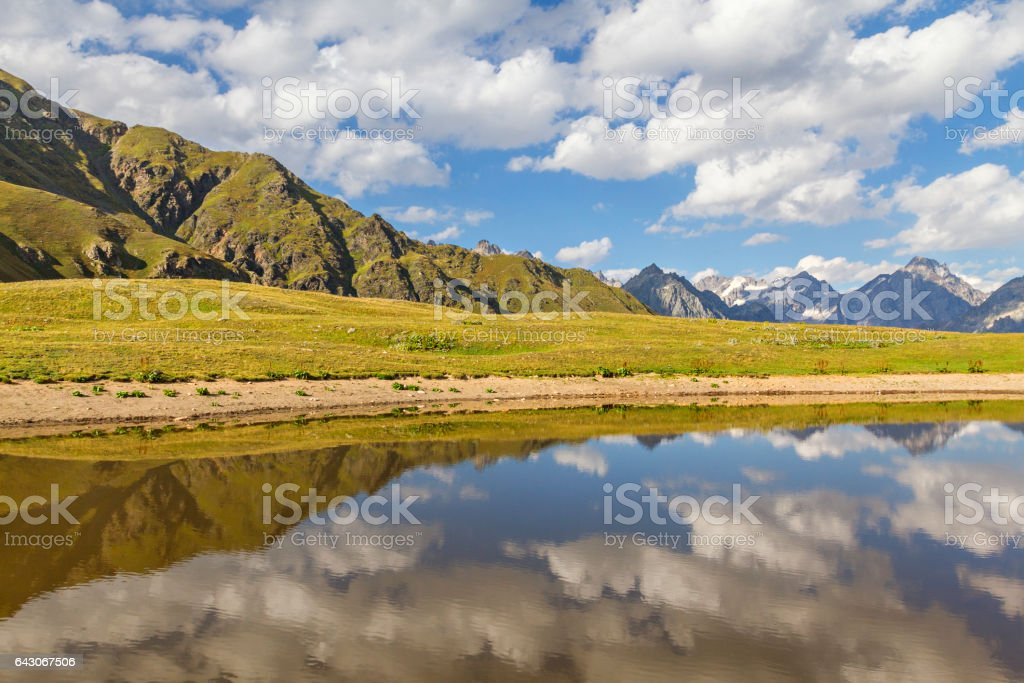 Reflection of clouds and mountains in the mountain lake in the Caucasus Mountains, Georgia stock photo