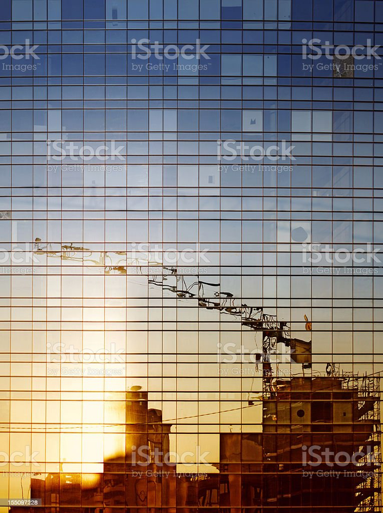 Reflection of construction work in a windowed building stock photo