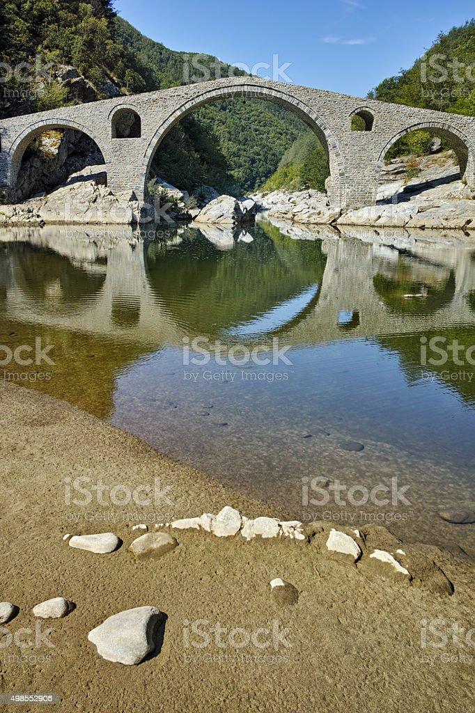Reflection of Devil's Bridge in Arda river stock photo