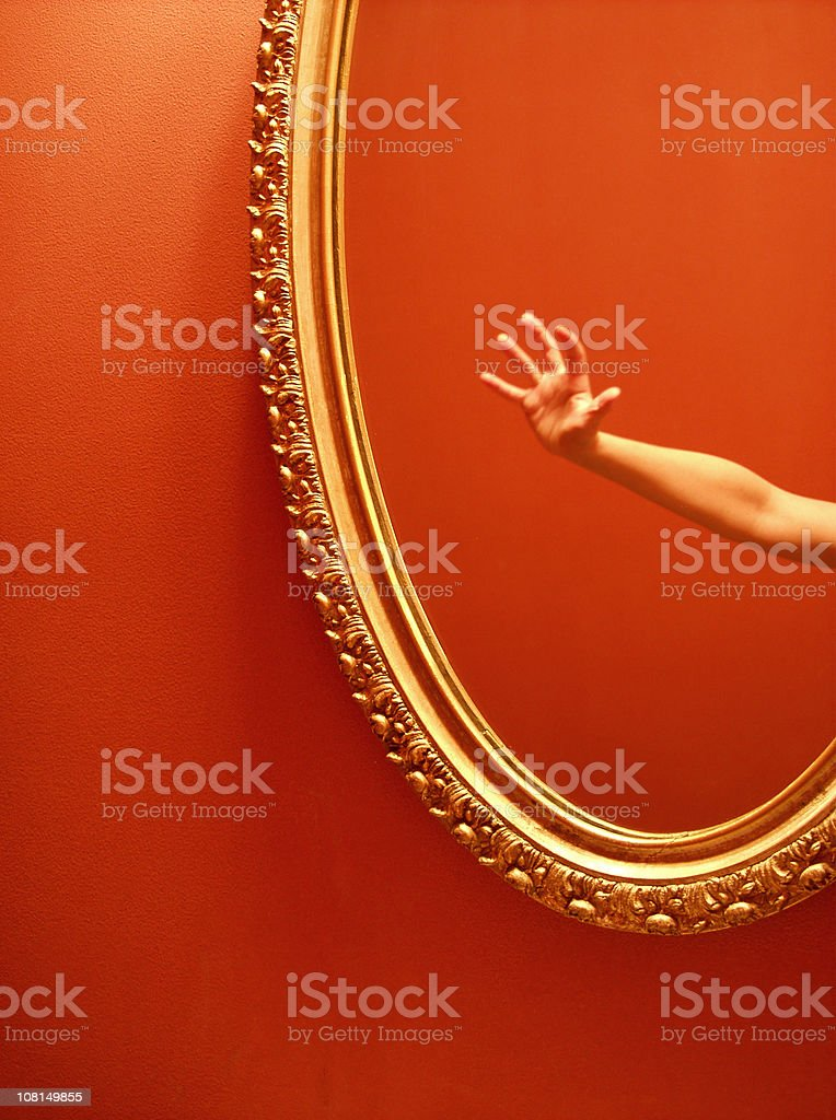 Reflection of Hand Reaching Out in Mirror royalty-free stock photo