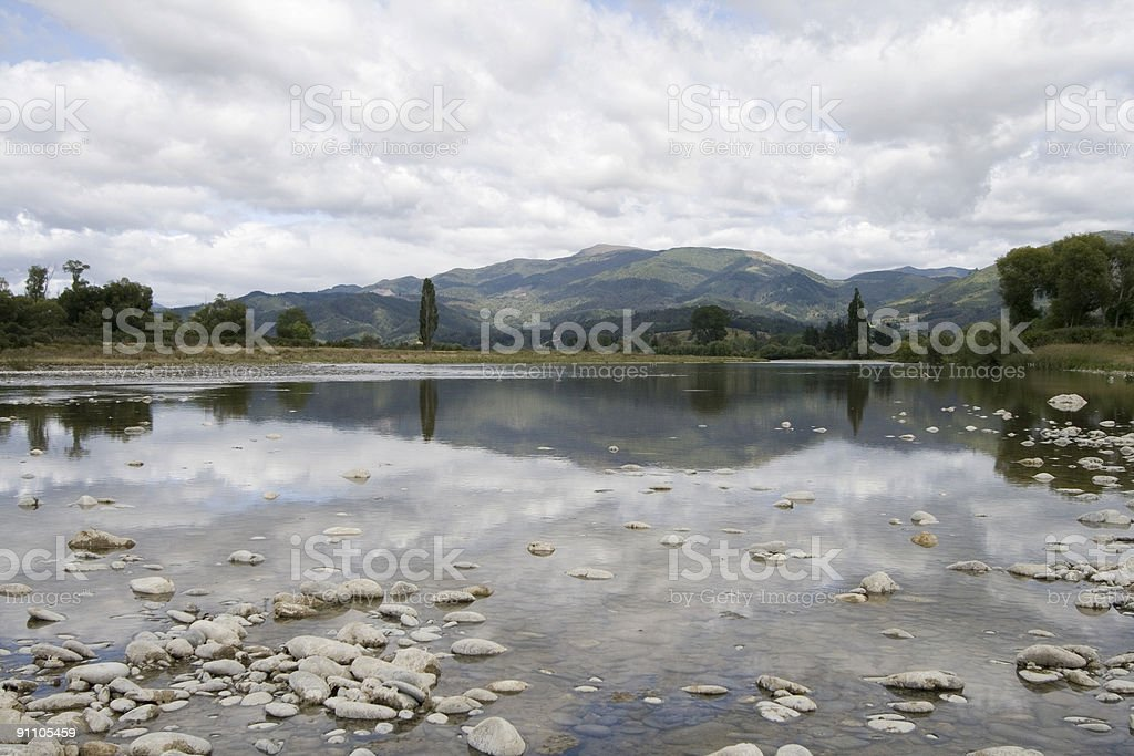 Reflection of hills on Motueka River, South Island, New Zealand stock photo