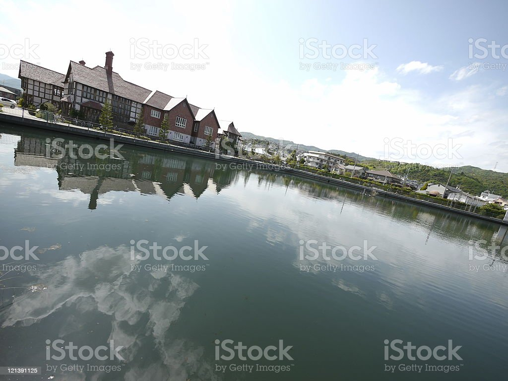 reflection of houses and the sky on pond stock photo