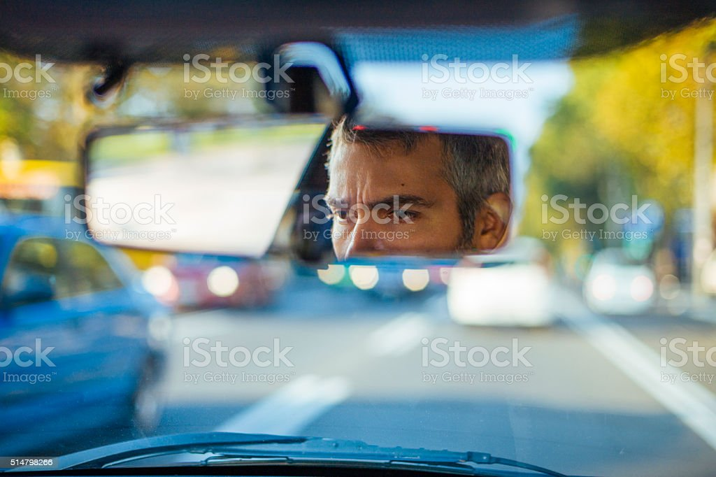 Reflection of man's eyes in the rearview mirror stock photo