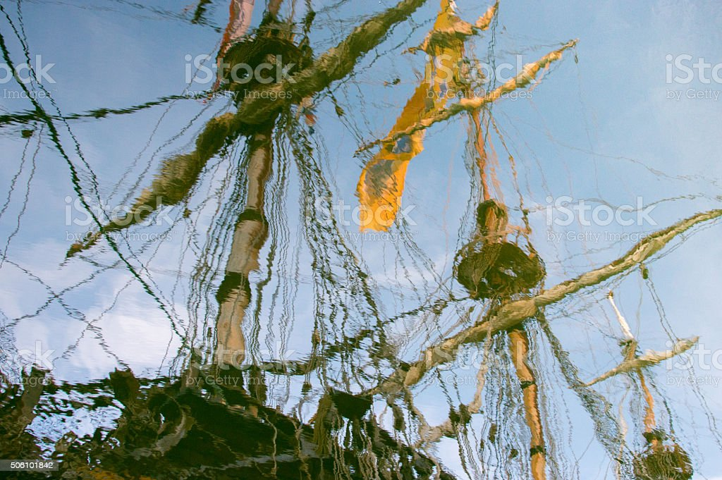 Reflection of masts of ancient vessel in the water stock photo