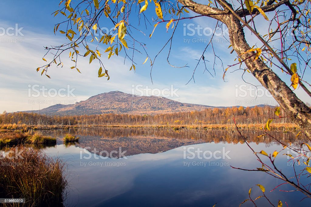 Reflection of mountain and sky in blue water stock photo
