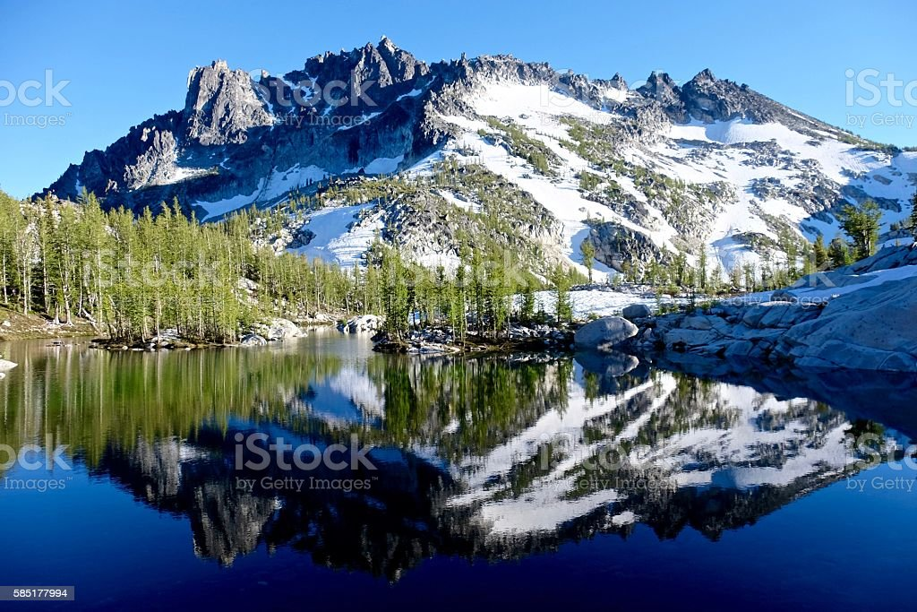 Reflection of mountain in alpine lake. stock photo