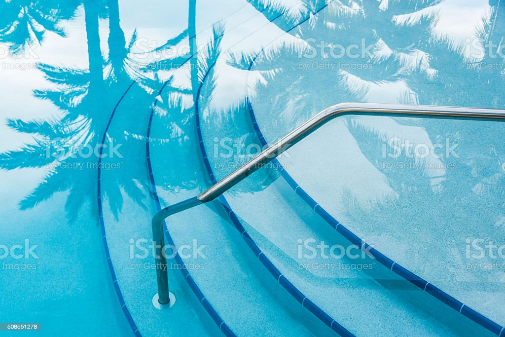 Reflection of palm trees over swimming pool with curved steps. stock photo