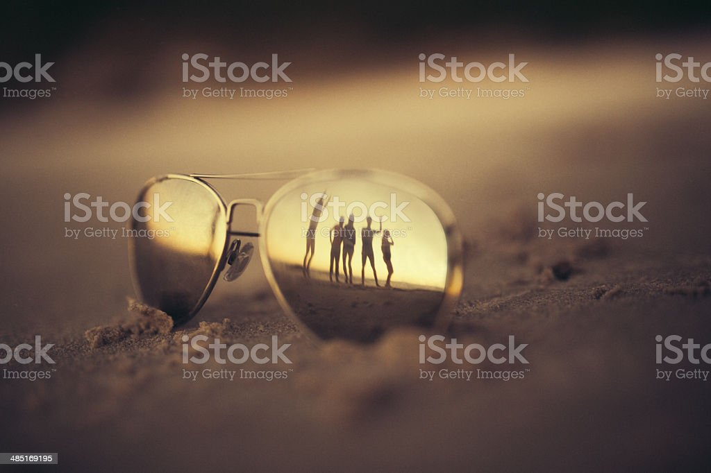 Reflection of people in sunglasses on beach stock photo