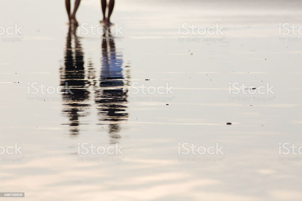 Reflection of two people walking in wet sands beach stock photo