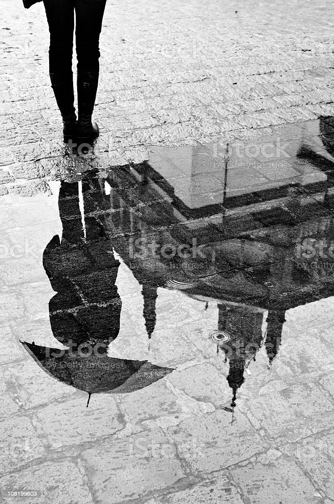 Reflection of Woman and Cathedral in a Puddle stock photo