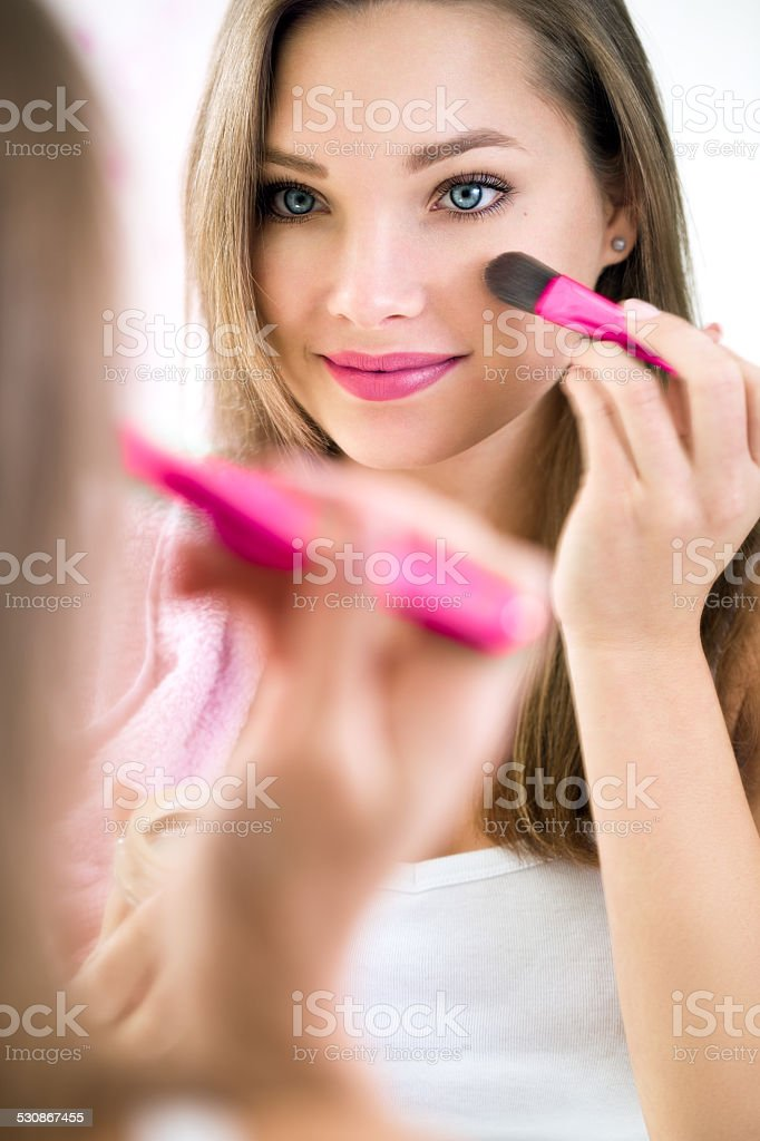 Reflection of young beautiful woman applying her make-up stock photo