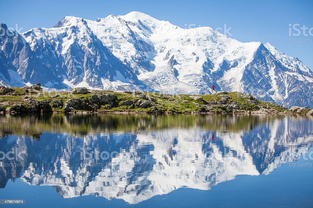 Reflection on crystal clear alpine lake, running man stock photo