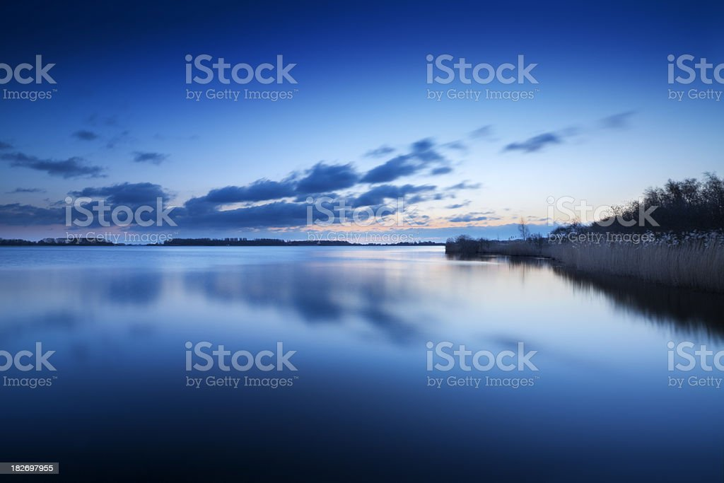 Reflections in a still lake at dawn in The Netherlands royalty-free stock photo