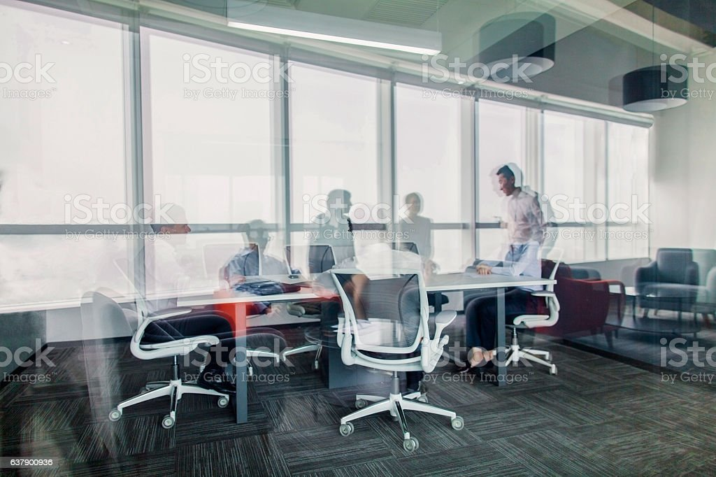Reflections of business colleagues having meeting in office stock photo