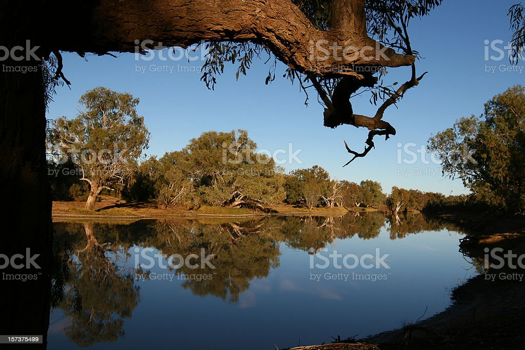 Reflections of trees and sky on a calmly flowing river stock photo