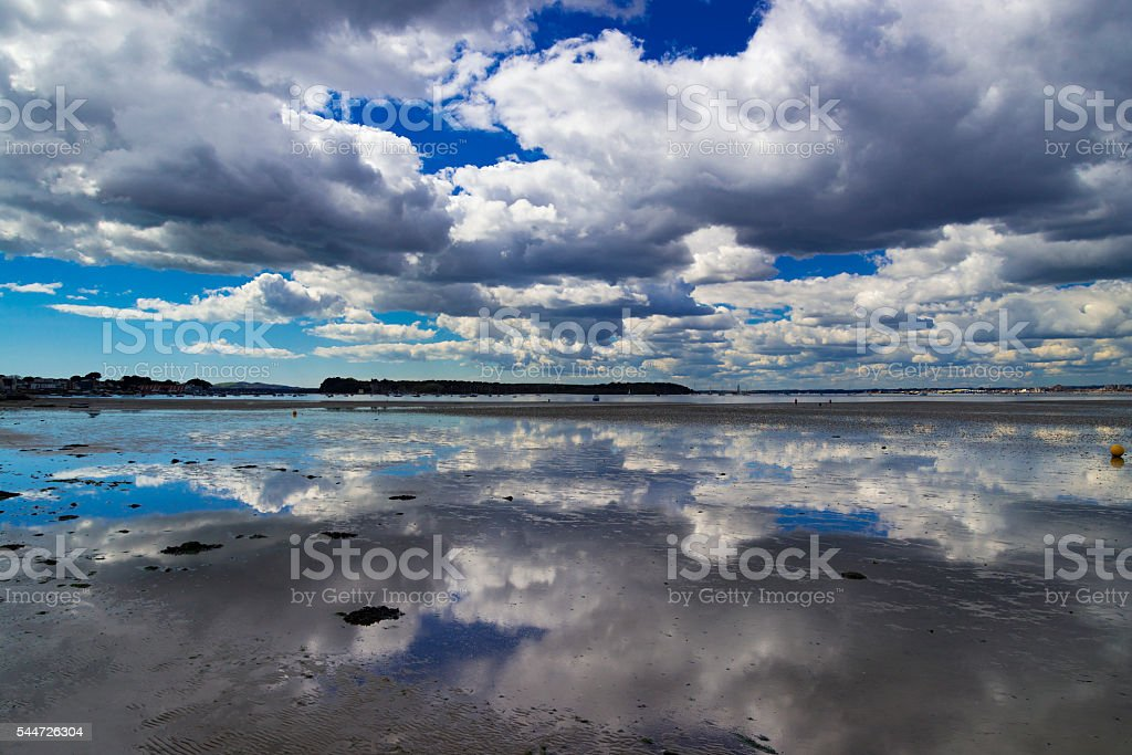 Reflections on wet sand in Poole Harbour stock photo