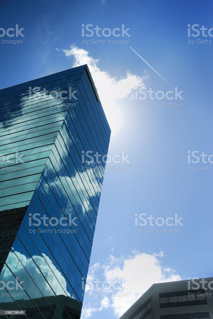 Reflective Skyscraper With Sky and Sun Behind Building royalty-free stock photo