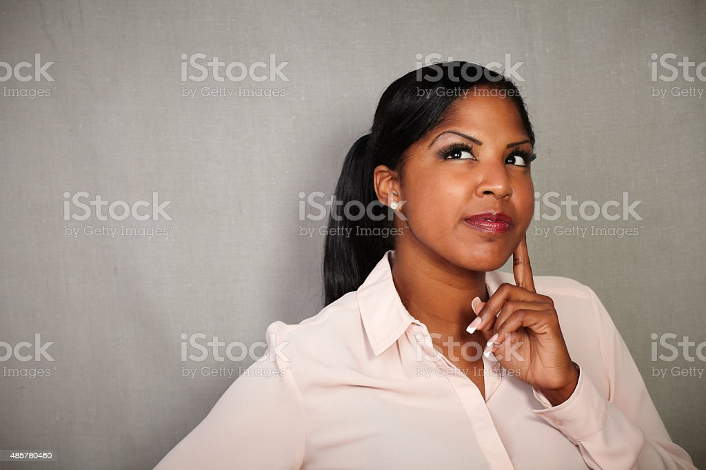Reflective woman contemplating with hand on chin stock photo