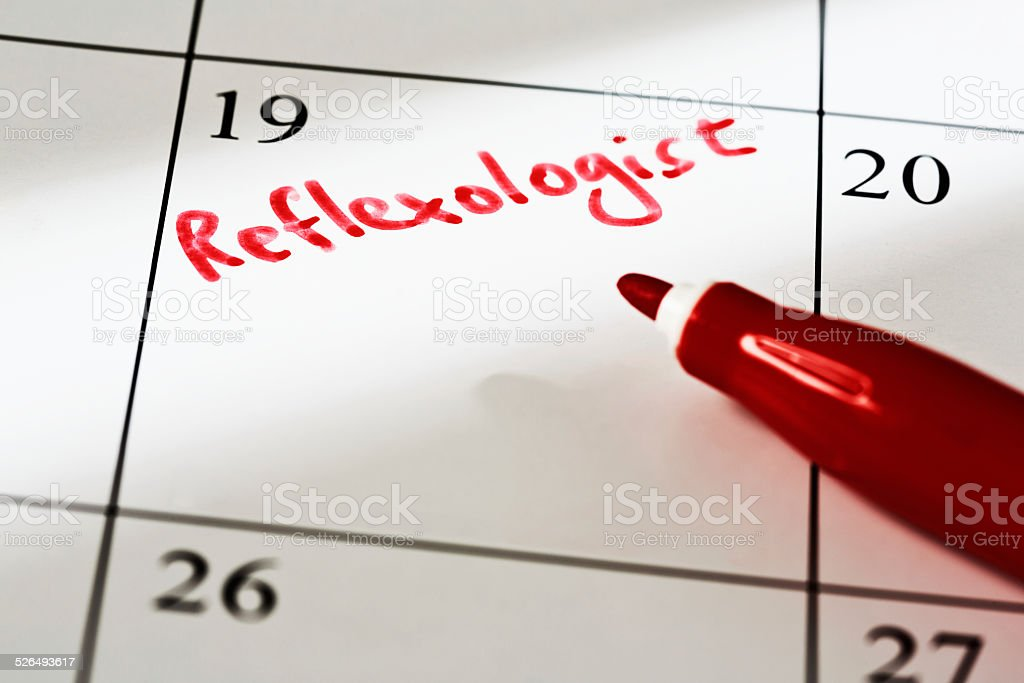'Reflexologist' appointment marked in red on calendar stock photo