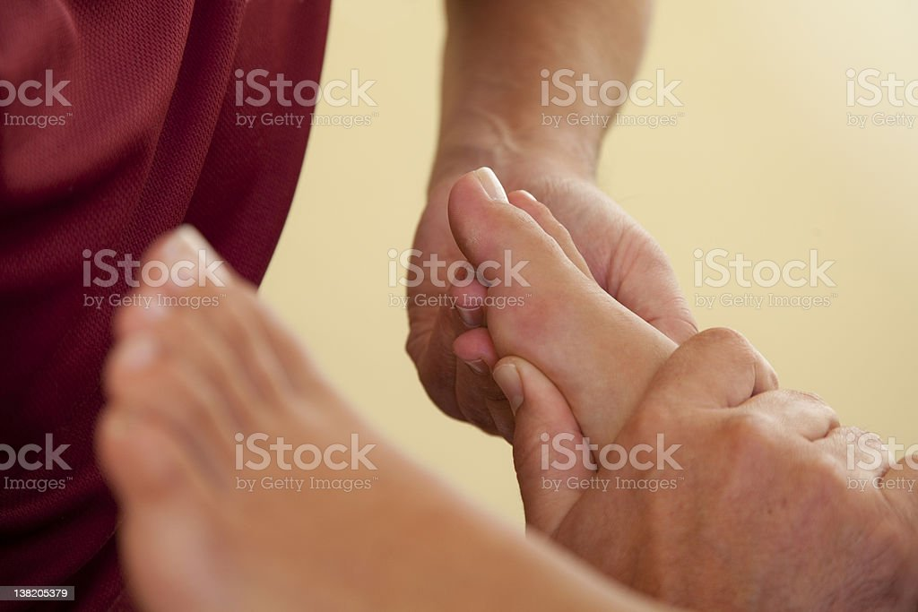 reflexology massage of female foot and toe royalty-free stock photo