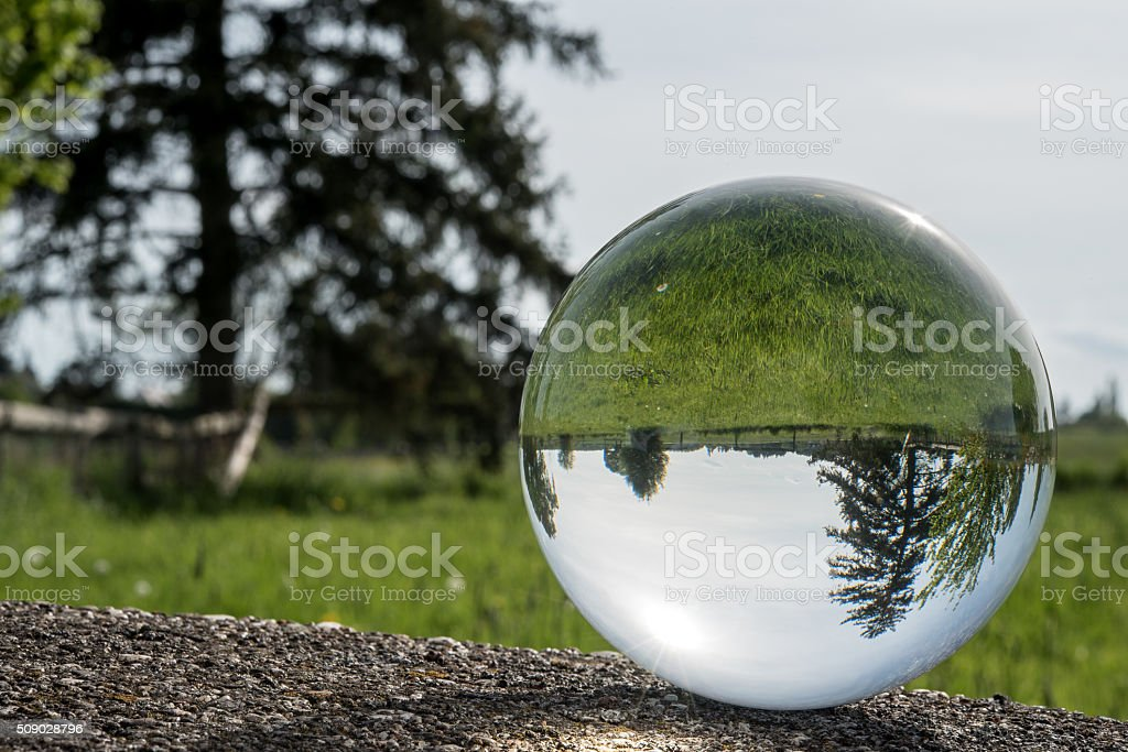 refraction of landscape in a big glass sphere stock photo