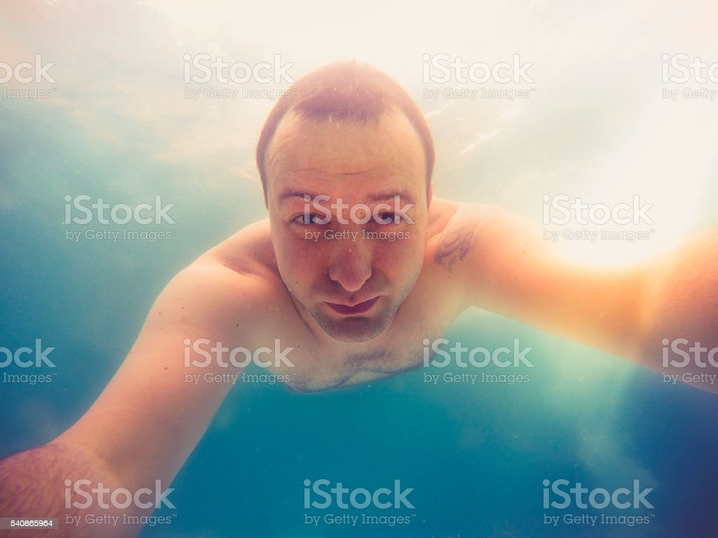 Refreshing at pool. Underwater wide angle selfie shot. stock photo