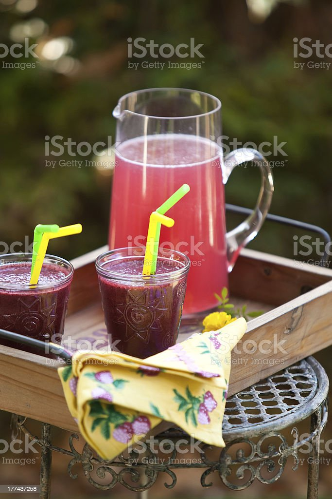 Refreshing berry drink in jar and glasses royalty-free stock photo