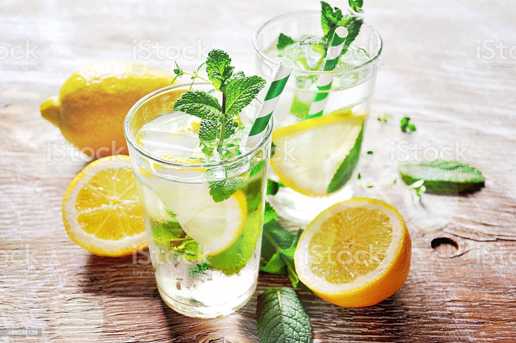 Refreshing cold iced mint tea with lemons and ice cubes stock photo