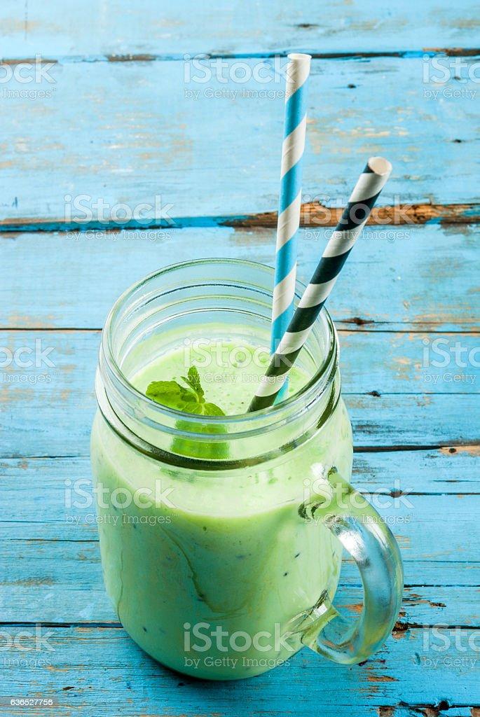 Refreshing green smoothie or milkshake in mason jar stock photo