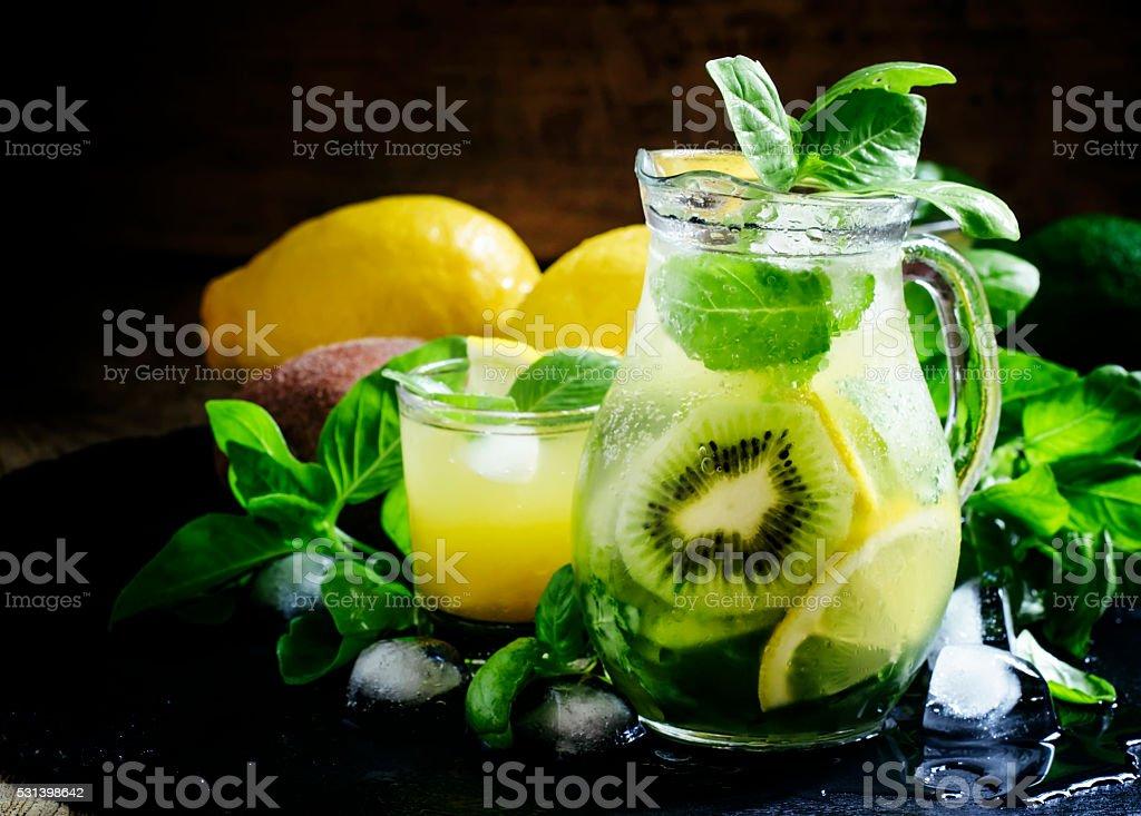Refreshing summer cocktail with green basil, lemon, kiwi fruit stock photo