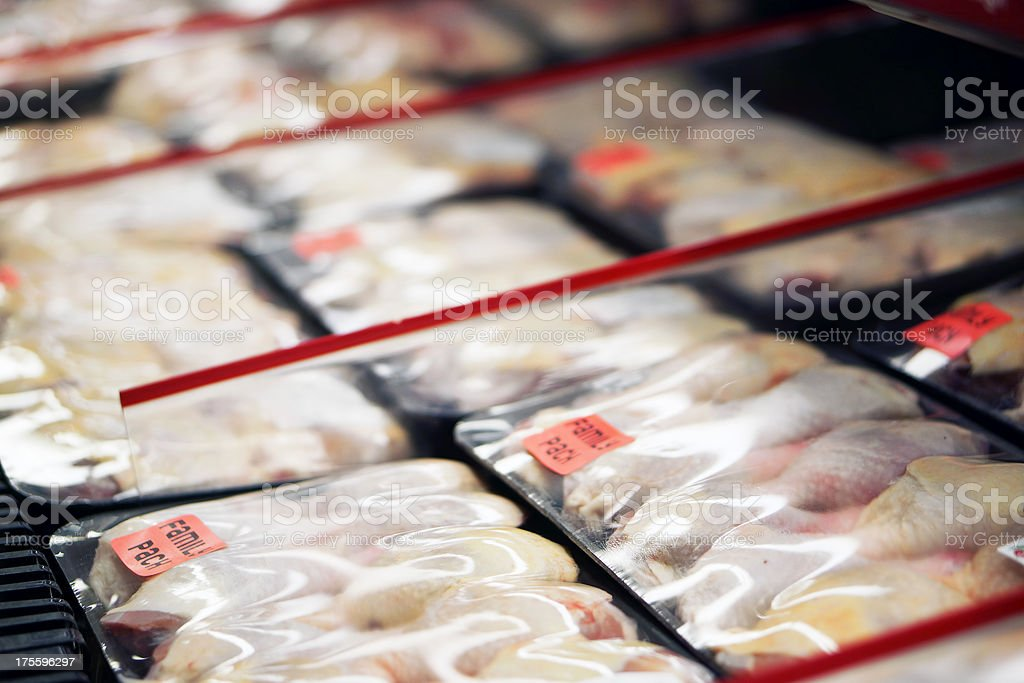 Refrigerated chicken legs in store stock photo