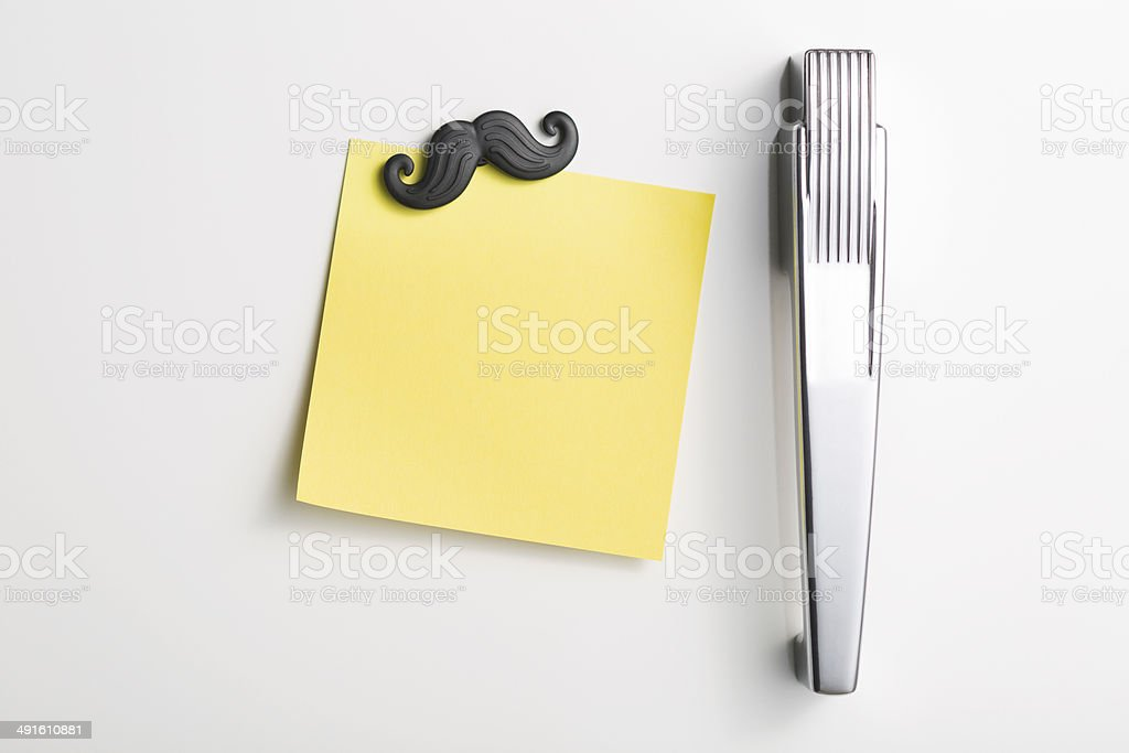 Refrigerator door with blank note and moustache stock photo