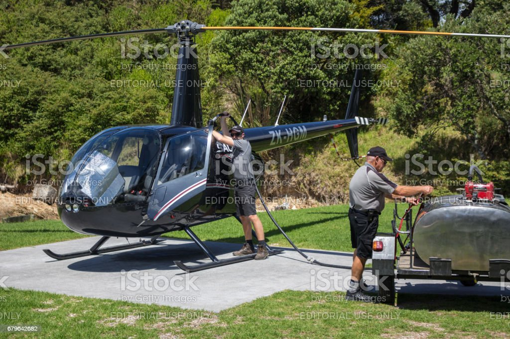 Refueling a Robinson R44 Raven II helicopter. stock photo