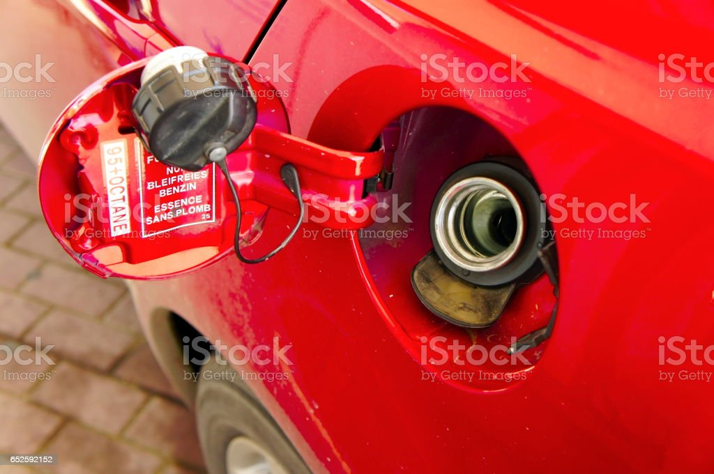 Refuelling fuel tank red car close-up stock photo