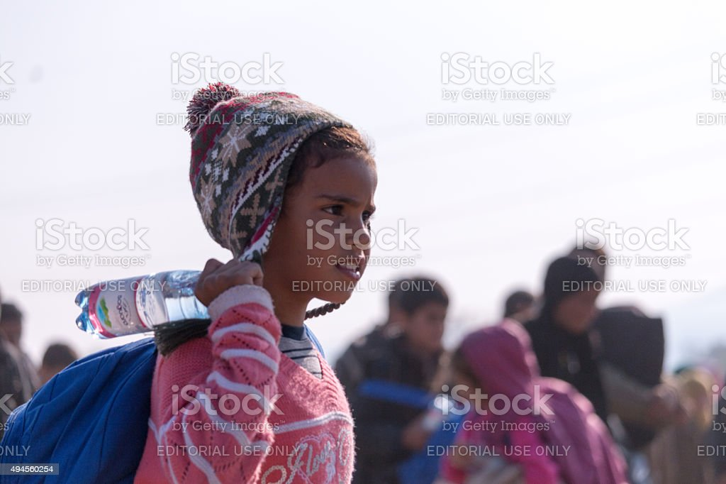 Refugee child with a backpack and a bottle of water stock photo
