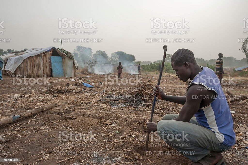 Refugee digs hole in displaced persons camp, Juba, South Sudan. stock photo