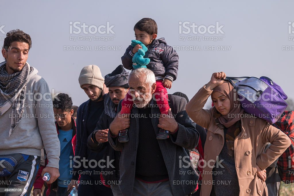 Refugee family with child on shoulders stock photo