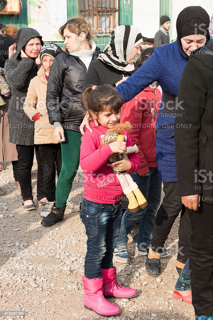 Refugee girl with rag doll in food line stock photo