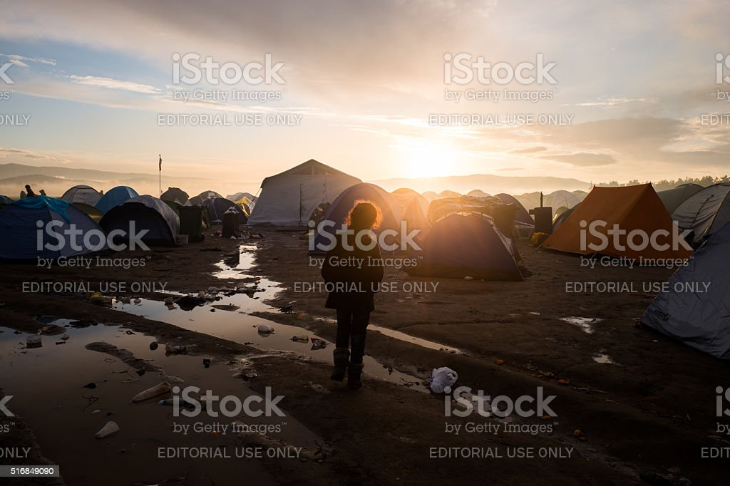 Refugee kid among tents stock photo