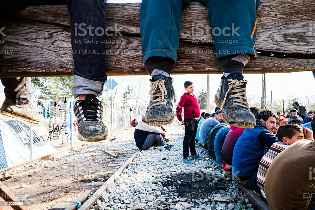 Refugee kids playing at train tracks stock photo