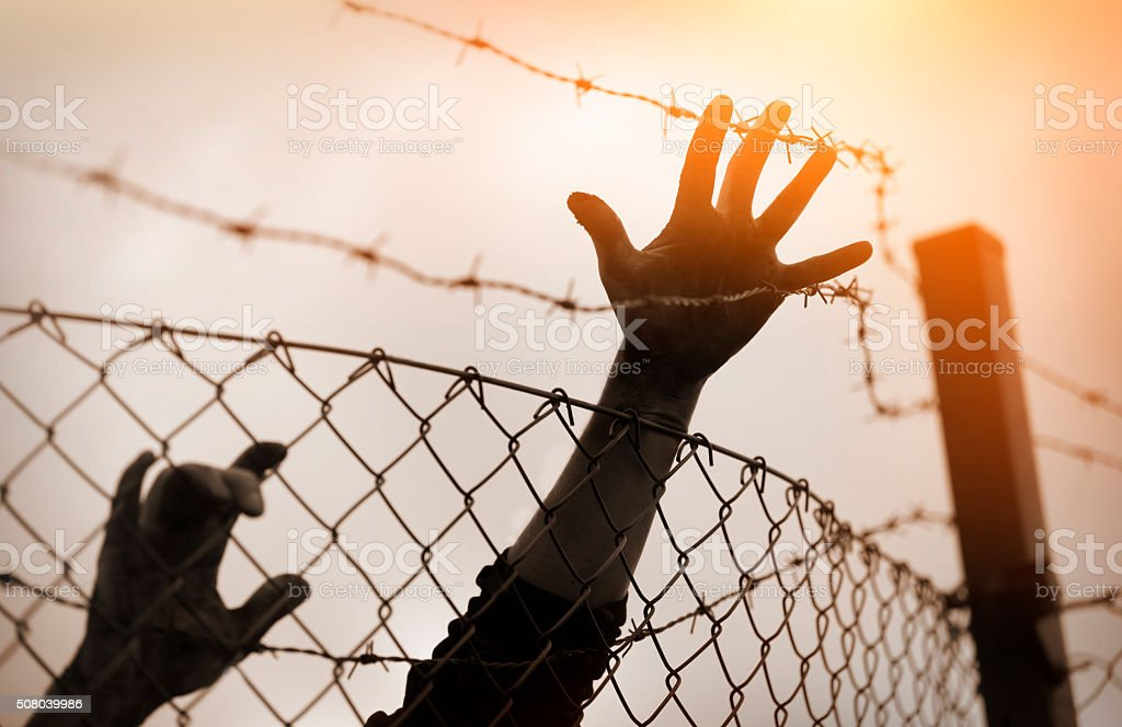 Refugee men and fence. Refugee concept stock photo