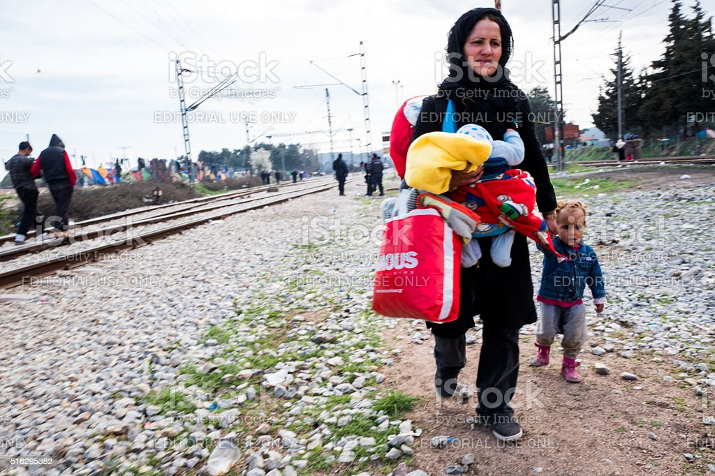 Refugee mother and child along train tracks stock photo