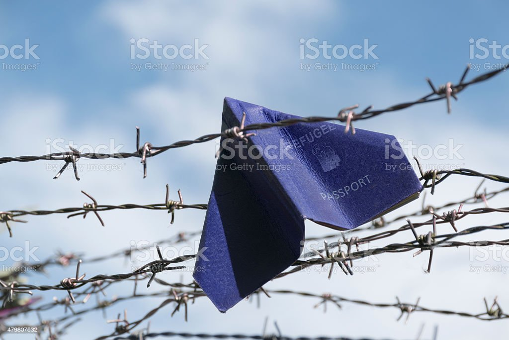 refugee passport as a paper plane in a barbed wire stock photo