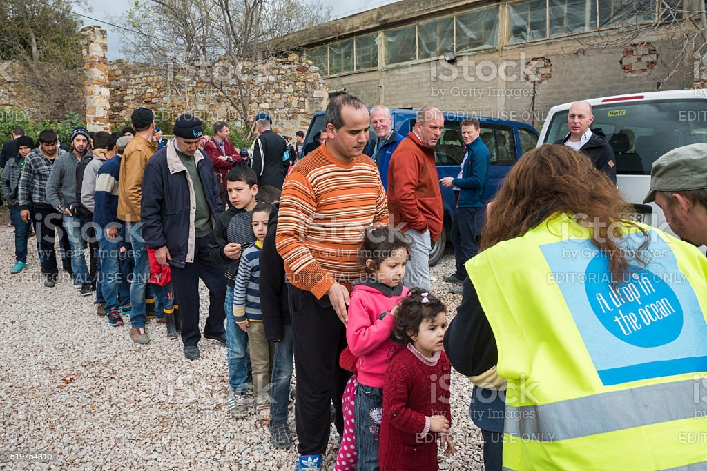 Refugees, volunteers and EU officials in Greek refugee camp stock photo