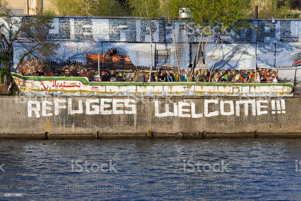 Refugees welcome graffiti and refugee boat in Berlin stock photo