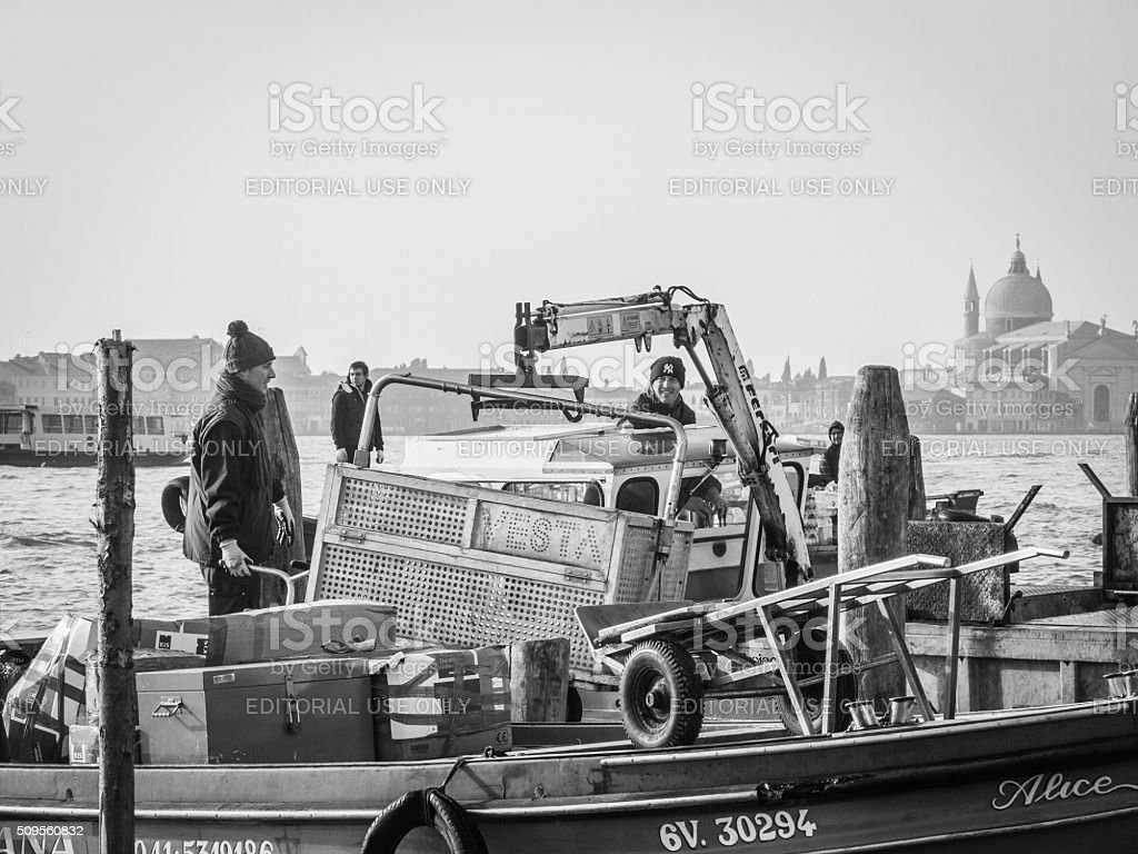 Refuse collectors unloading containers of rubbish into boats for stock photo