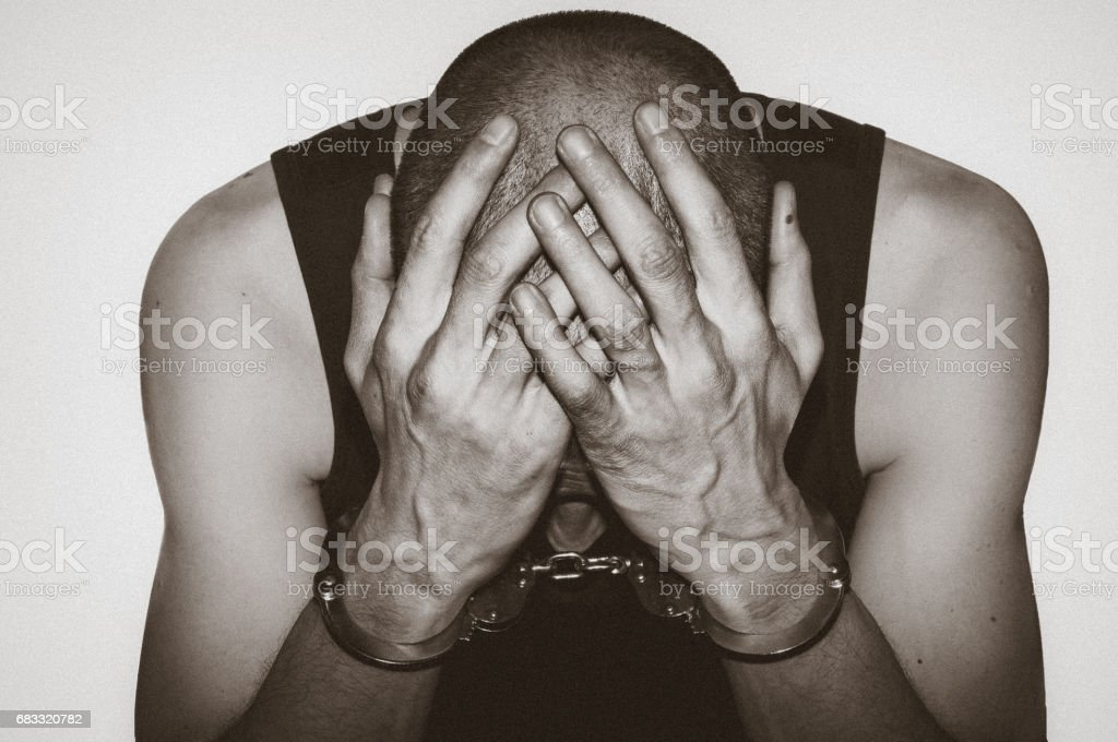 Regret. Arrested man with handcuffs on his hand regret for being caught. Crime concept. With hard film grain. stock photo