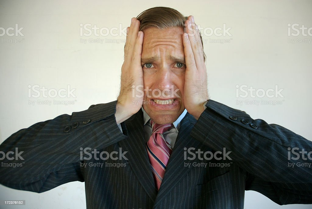 Regretful Businessman Holding Head After Mistake stock photo