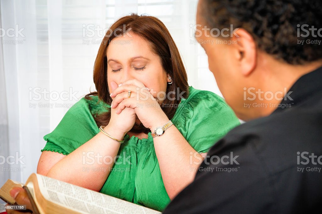 Regretful woman prays eyes closed while clergyman reads her Bible stock photo