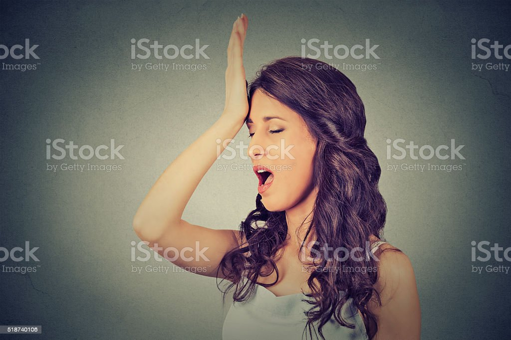 Regrets wrong. Woman slapping hand on head duh moment stock photo